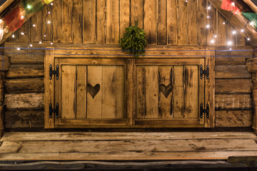 Christmas lights on the wooden cabin window with heart decoration