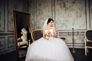 Young beautiful bride is sitting in an armchair.