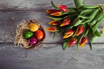 tulipani e uova pasquali su sfondo di legno