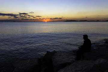Scenic view of beautiful sunset with a fisherman silhouette sitting on the rocks near seaside