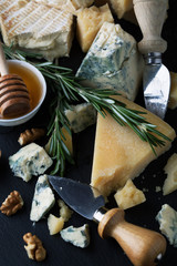 Delicious cheeses on a board with honey, nuts and wine