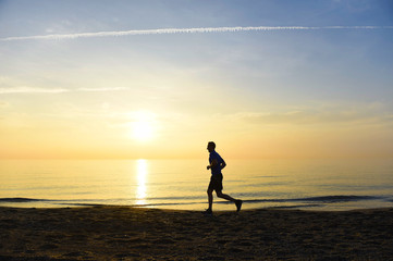 silhouette young sport man running outdoors on beach at sunset with orange sky