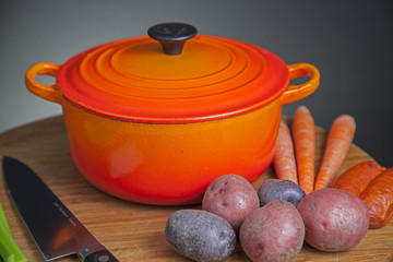 Orange enamel Dutch oven on cutting board with vegetables and cutlery on one side