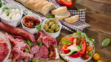 Italian antipasto on wooden table.