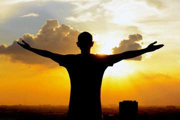 Silhouette of a man raising his arms on  twilight sky background