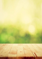 Wood table top on green bokeh abstract background, vintage tone