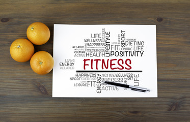 Wooden background with oranges and text: Fitness word cloud, fit