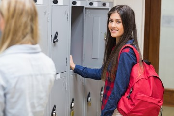 Smiling students using locker