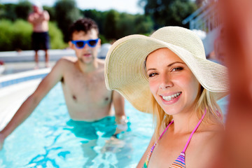Couple in the swimming pool taking selfie. Summer and water.