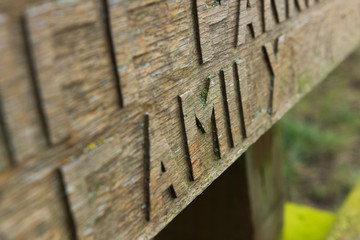 Hand carved chiseled letters on an old wooden bench covered in moss