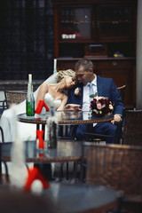 Romantic relaxed newlywed couple sitting at restaurant table