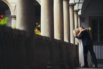 Romantic newlywed valentine couple kissing on antique balcony wi