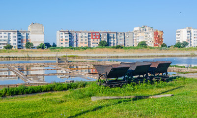 an iron cart used for transportation of salt in bulgarian city pomorie stands in front of a salt lake surrounded by multi storey houses.