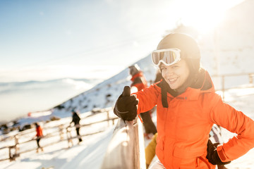 Woman skier on slopes. Portrait of young woman smiling in skiing equipment, wearing goggles and helmet