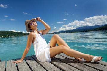 Junge Frau sitzt im Sommer am See auf dem Bootssteg. Wörthersee. Kärnten. Österreich