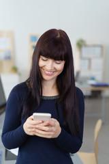 frau im büro schaut lächelnd auf ihr smartphone