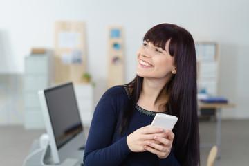 glückliche frau mit ihrem smartphone im büro