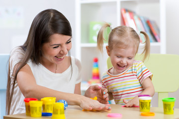 Young pretty woman and child girl playing with colorful clay in nursery