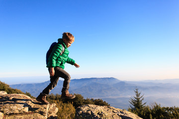 little boy hiking in scenic mountains
