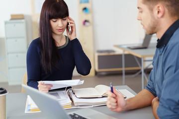 junge frau im büro hält einen brief in der hand und telefoniert