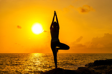 Woman practices yoga on the rocks against the sea