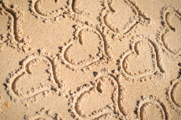 Hearts drawn on texture of sand background