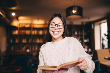 Student girl laughing and holding a book in library