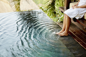 A person sitting on a bench with her feet in the shallow water of a pool, making ripples.