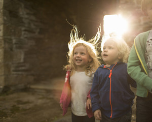 Two children on a farm, looking upwards with curiosity and excitement.