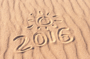 Sign 2016 and sun written on sandy beach. Summer travel concept