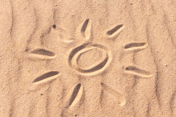 simple sun drawing in the sand on The beach. Summer travel concept