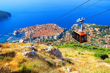 Cable car with tourists and Dubrovnik Old town in background Wall mural