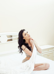 Sexy beautiful brunette woman lying in bed in sensual gray lingerie, looking at camera. Seduction concept in luxury room interior