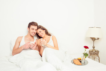 Cute couple in love at home embracing each other having breakfas