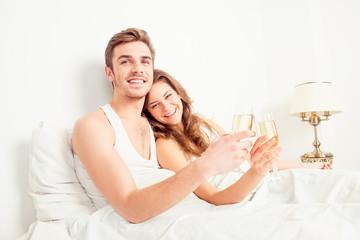 Cheers! Happy couple in love celebrating honeymoon in bedroom wi