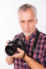 Portrait of aged photographer holding camera and going to make p