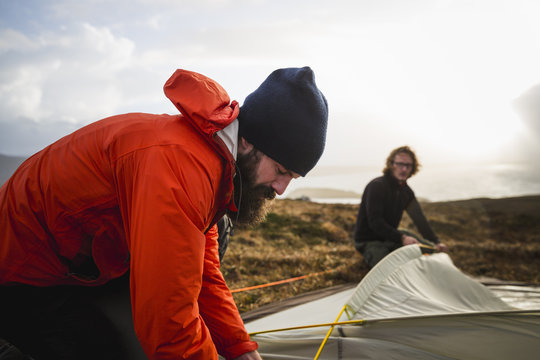 Two men holding and putting up a small tent in open space. Wild camping.