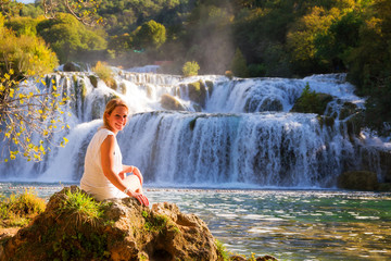 Stunning young woman sitting at a waterfall in Krka national park. Wearing a white dress in summer, smiling lovely over her shoulder