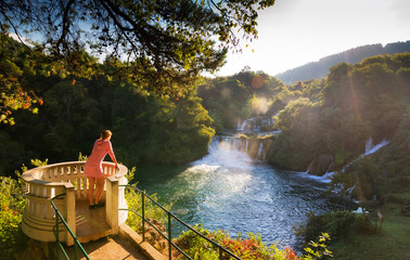 Young woman looks over the waterfalls of the Krka river in Krka national park in Croatia