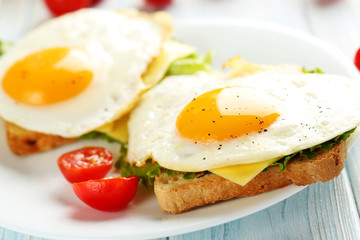 Fried eggs with toasts on plate on blue wooden table