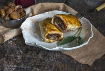 Homemade pork sausage rolls with chestnuts, cranberry sauce and sage
