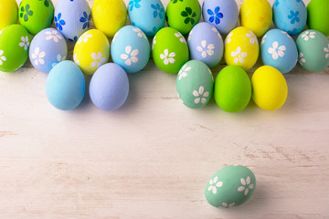 Pastel colored Easter eggs on a white wooden background, copy space