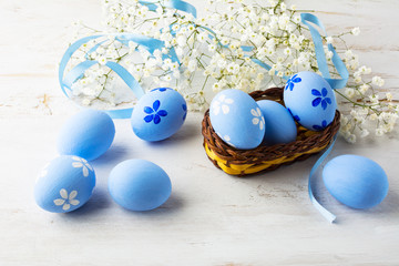 Blue Easter eggs in a small wicker basket and small white baby's breath flowers on white wooden background