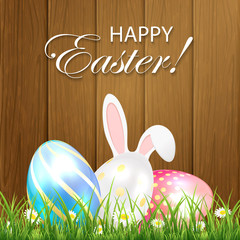 Easter background with shiny eggs and rabbit on wooden backgroun
