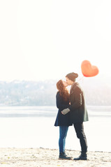 Young couple in love, at the riverside, with a red balloon, kissing
