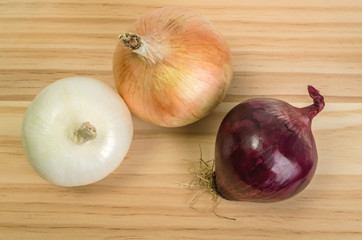 Whole Red, White and Yellow Onions on Cutting Board Waiting to be Cut