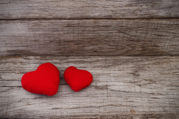 Two red hearts on wooden background.