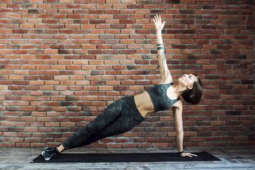 tattooed female doing exercises indoors, sporty woman practicing yoga