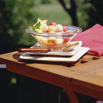 Fruit salad of melon balls outdoors.