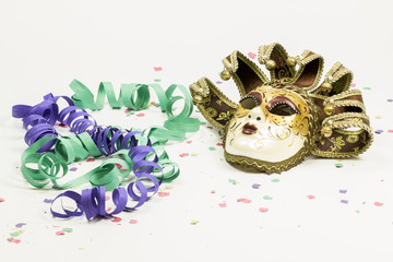 Carnival Venetian mask with confetti and streamers on white background